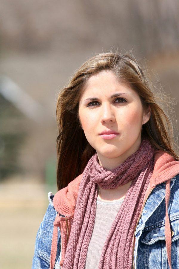 jonge vrouw buiten kijkend in de camera