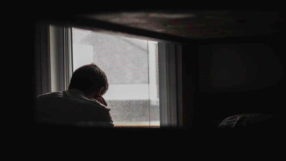 persoon eenzaam bij raam